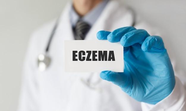 Médico segurando um cartão com o texto eczema