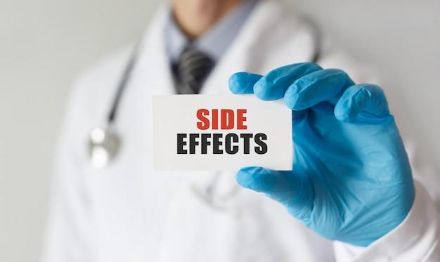 Médico segurando um cartão com o texto efeitos colaterais