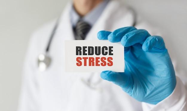 Médico segurando um cartão com o texto reduzir o estresse, conceito médico