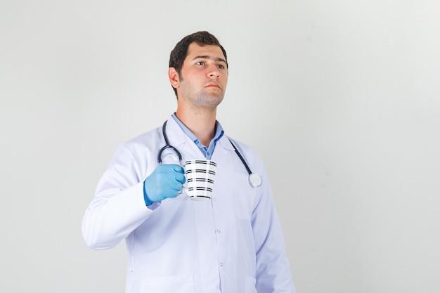 Médico segurando um copo de bebida no jaleco branco, luvas e olhando pensativo