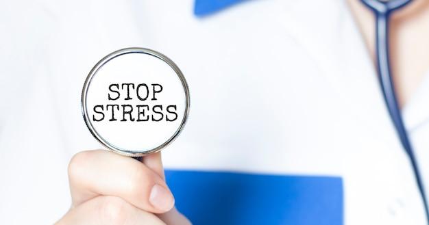 Médico segurando um estetoscópio com o texto stop stress, conceito médico