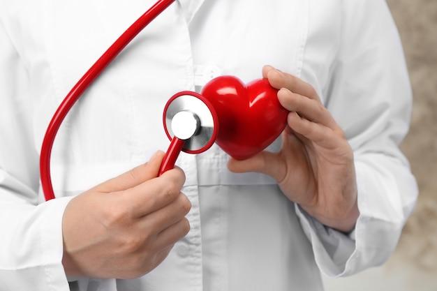 Médico segurando um estetoscópio e um coração de plástico, closeup