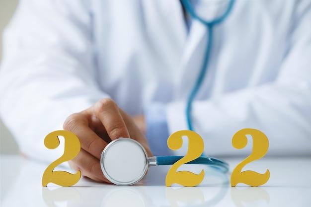 Médico segurando um estetoscópio perto de ouro de madeira número 2022 ideia para uma nova tendência no tratamento de medicamentos