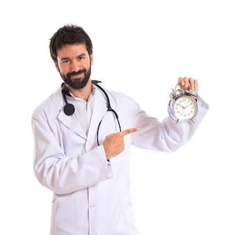 Médico segurando um relógio sobre fundo branco
