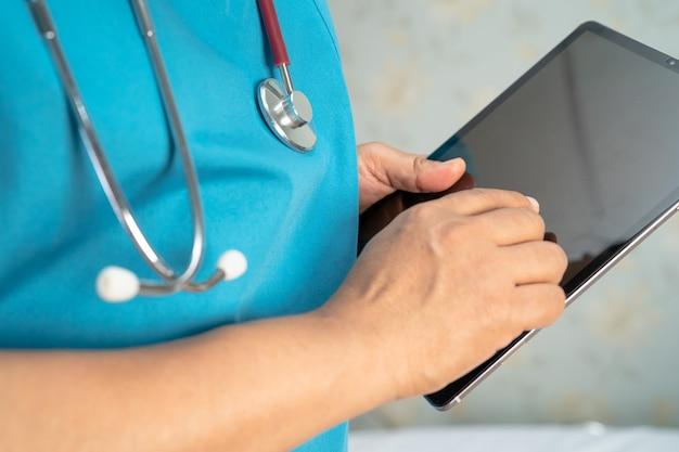 Médico segurando um tablet digital para pesquisar dados para tratar paciente em hospital de enfermagem