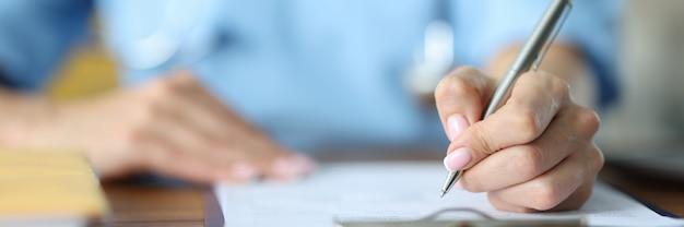 Médico segurando uma caneta de prata em documentos na mesa em close-up do escritório