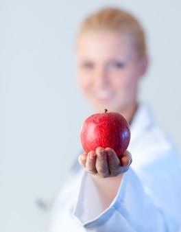 Médico segurando uma maçã com foco na maçã