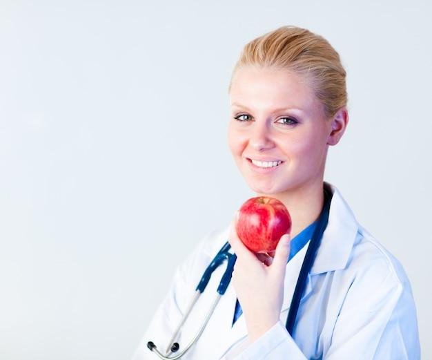 Médico segurando uma maçã com foco na pessoa