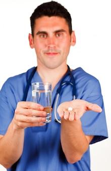 Médico segurando uma pílula e um copo de água