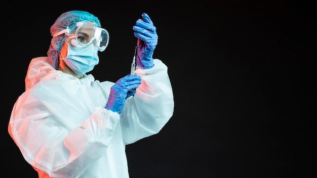 Médico segurando uma seringa com espaço de cópia