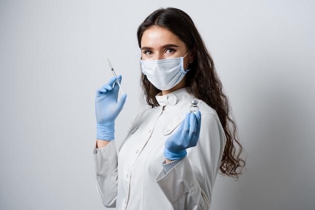 Médico segurando vacina contra coronavírus. garota atraente em luvas médicas com seringa e medicamentos