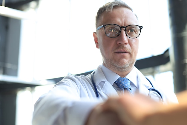 Médico sênior aperta a mão de um paciente.