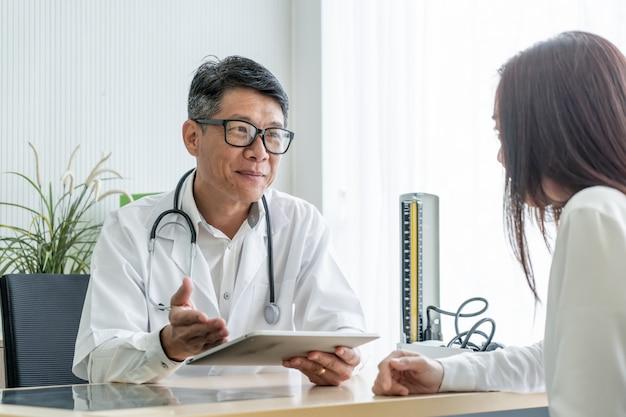 Médico sênior asiático e paciente estão discutindo