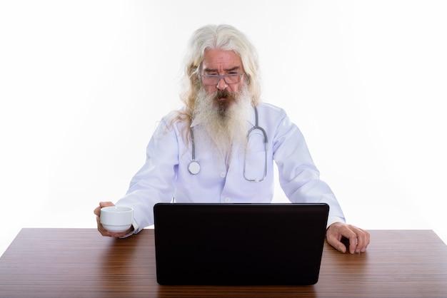 Médico sênior barbudo usando óculos enquanto usa laptop