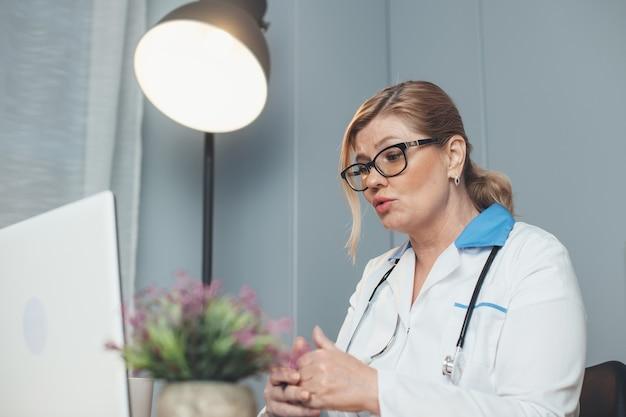 Médico sênior caucasiano está falando online com o paciente usando um laptop e usando óculos enquanto fala para a câmera