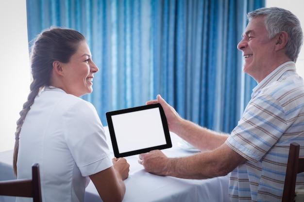 Médico sênior do sexo feminino e feminino usando tablet digital
