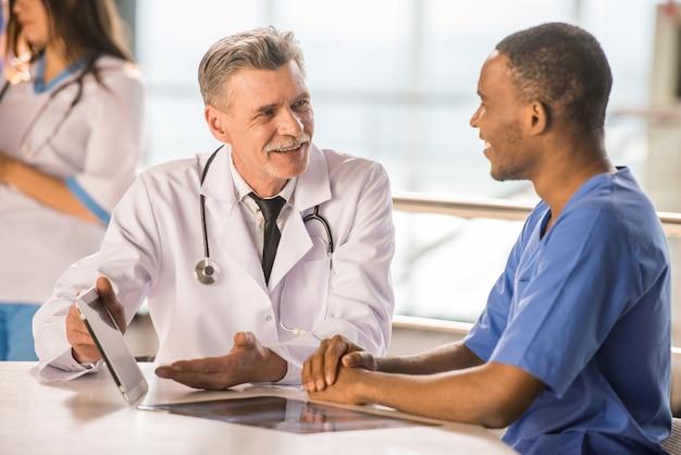 Médico sênior e jovem médico falando e usando um tablet.