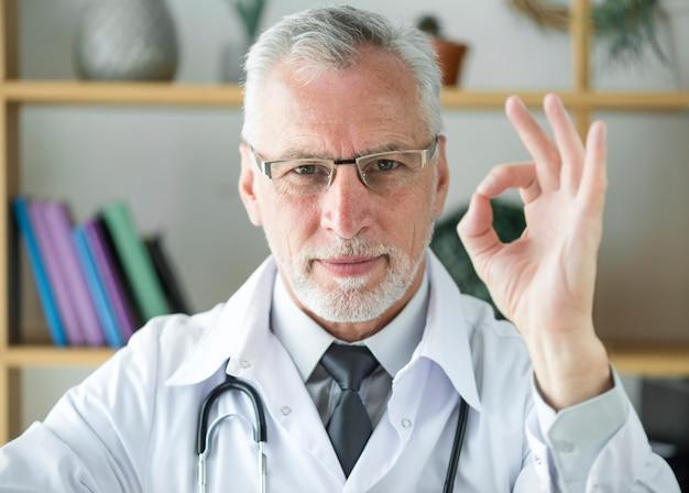Médico sênior, gesticulando, ok