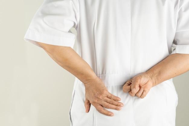 Médico sênior mulher que sofre de dor nas costas, tocando com a mão, dor muscular