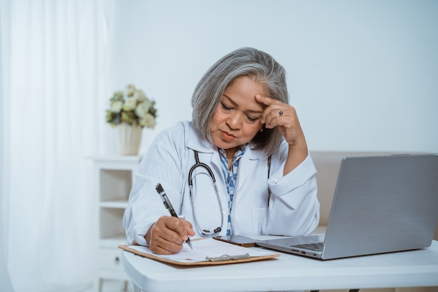 Médico sênior mulher usando laptop