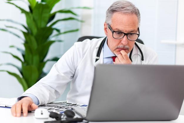 Médico sênior trabalhando em seu laptop em seu estúdio