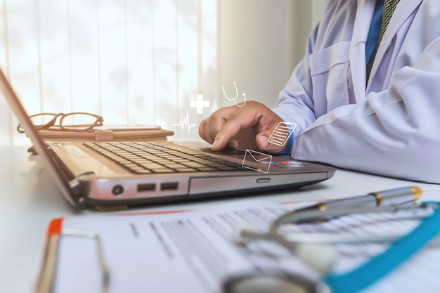 Médico sentado à mesa no hospital e digitando no computador portátil