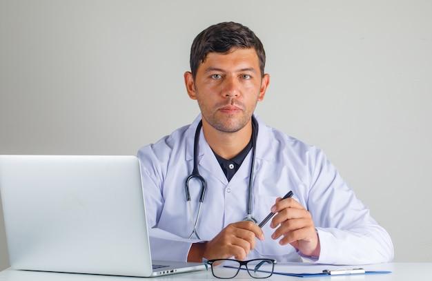 Médico sentado e segurando a caneta no jaleco branco e estetoscópio