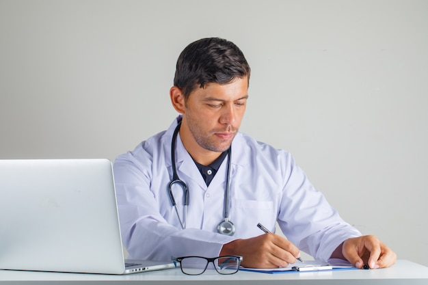 Médico sentado e tomando notas no jaleco branco e estetoscópio