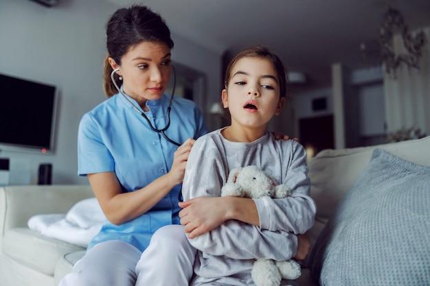 Médico sentado no sofá ao lado da garota e examinando seus pulmões com o estetoscópio. médico em serviço ao domicílio.
