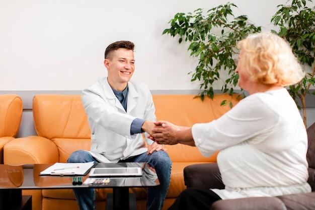 Médico sentado no sofá e segurando a mão do paciente