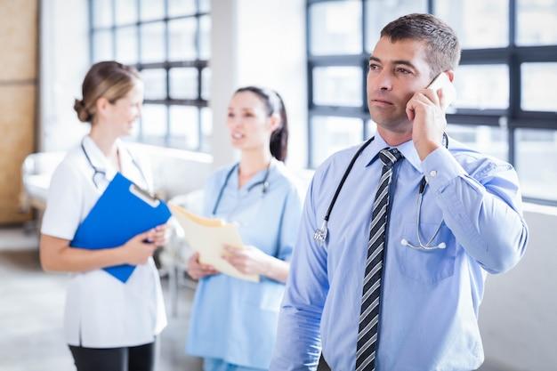 Médico sério ao telefone no hospital