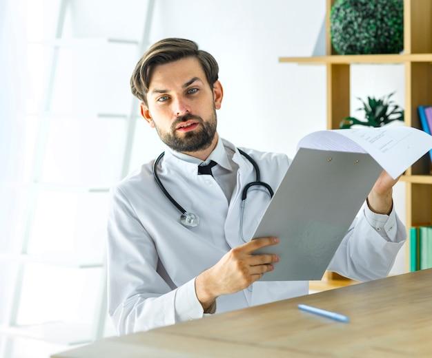 Médico sério com prancheta, olhando para a câmera