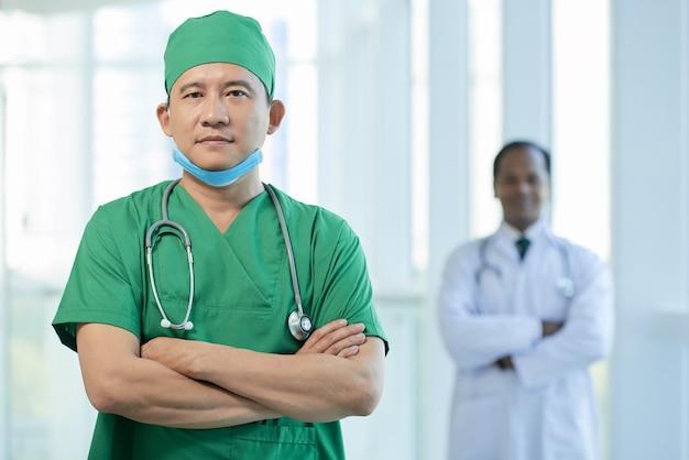 Médico sério e confiante em uniforme verde cruzando os braços e olhando para a câmera