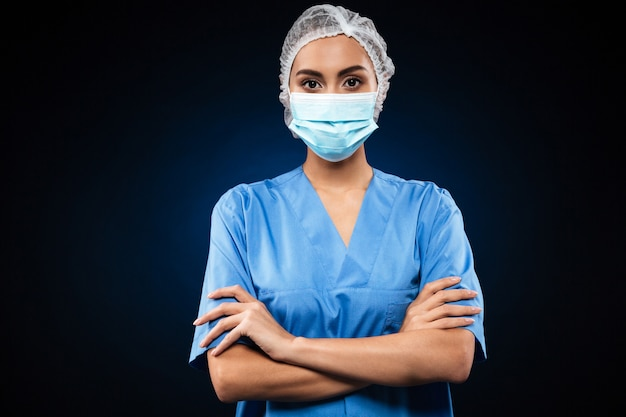 Médico sério em máscara médica e boné olhando