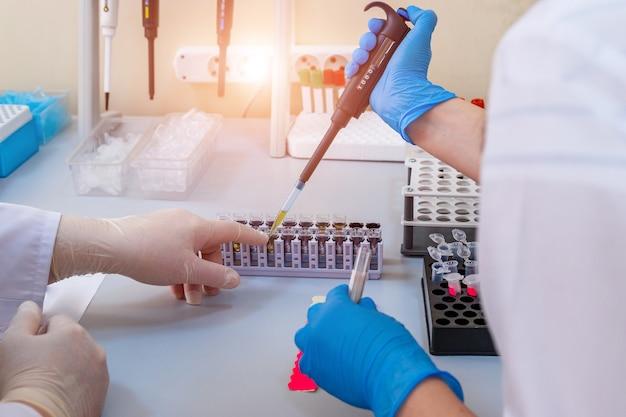 Médico sério estudando elemento químico em laboratório. laboratório de hematologia. diagnóstico de pneumonia. covid-19 e identificação de coronavírus. pandemia. conta-gotas com sangue.