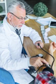 Médico sério, medição de pressão arterial do paciente