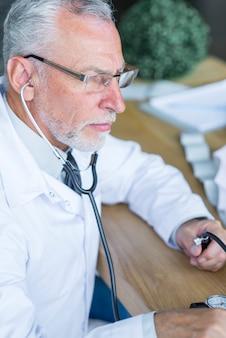 Médico sério, medição de pressão arterial