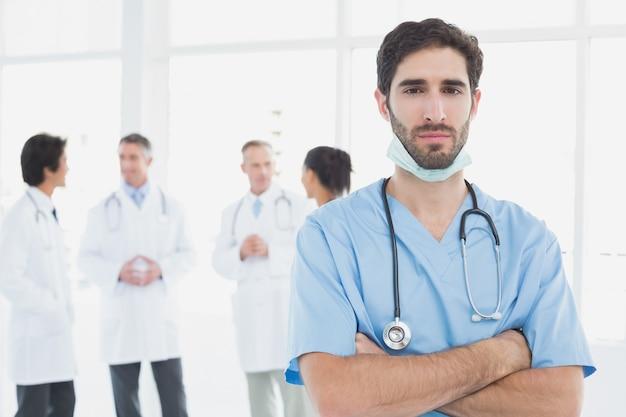 Médico sério, olhando para a câmera com os colegas por trás dele