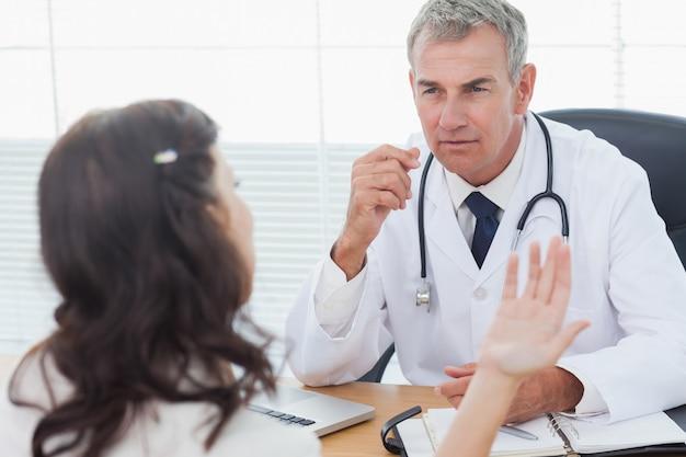 Médico sério, ouvindo seu paciente falando em cirurgia brilhante