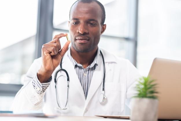 Médico sério vestindo uniforme esterilizado e mantendo o estetoscópio ao redor do pescoço enquanto olha para o pequeno tablet
