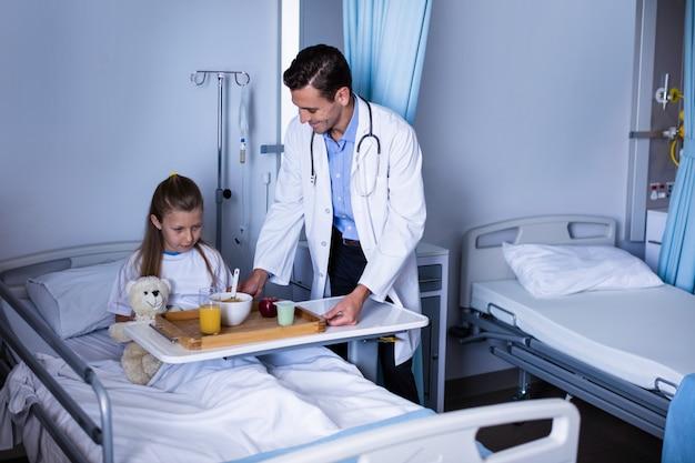 Médico servindo café da manhã para menina