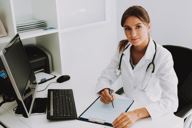 Médico simpático praticante está escrevendo no escritório