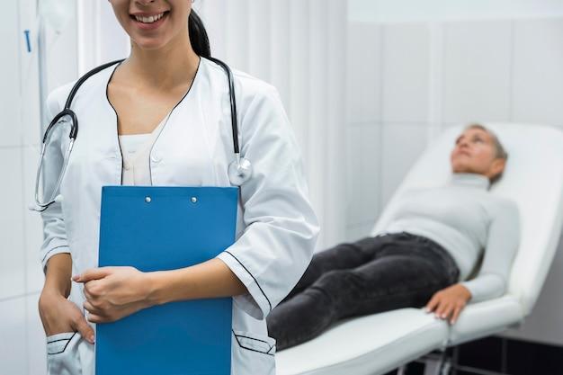 Médico sorridente ao lado de paciente desfocado