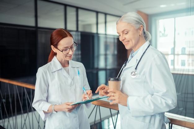 Médico sorridente. close de uma médica caucasiana sorridente, escrevendo na prancheta, ao lado de seu colega Foto Premium