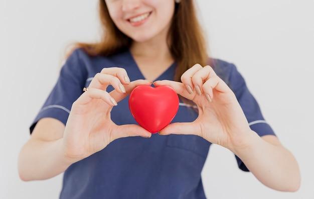 Médico sorridente close-up, segurando o brinquedo em forma de coração