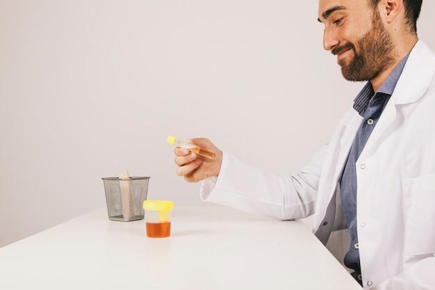 Médico sorridente com um teste de urina em sua mesa