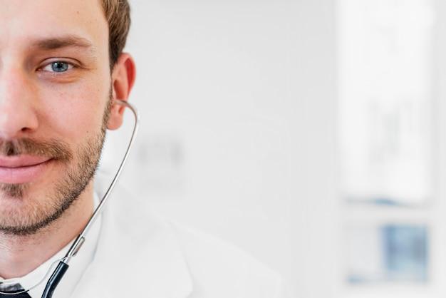 Médico sorridente de close-up com estetoscópio