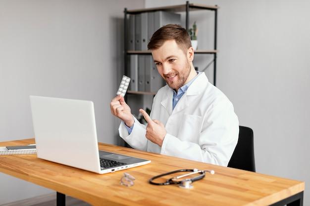 Médico sorridente de tiro médio na mesa