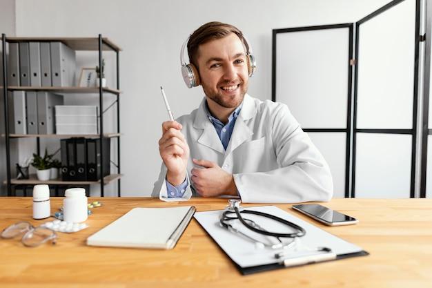 Médico sorridente de tiro médio segurando caneta