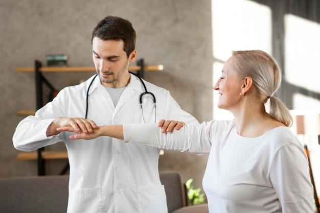 Médico sorridente de tiro médio verificando mulher